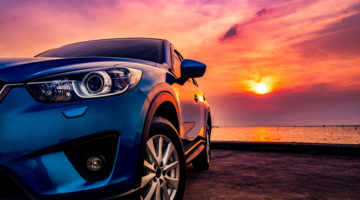 Blue compact SUV car with sport and modern design parked on concrete road by the sea at sunset. Environmentally friendly technology. Business success concept. New Car features 2020
