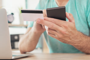 Online shopping with credit card and smart phone, casual man is using smartphone app in home office to purchase items on internet
