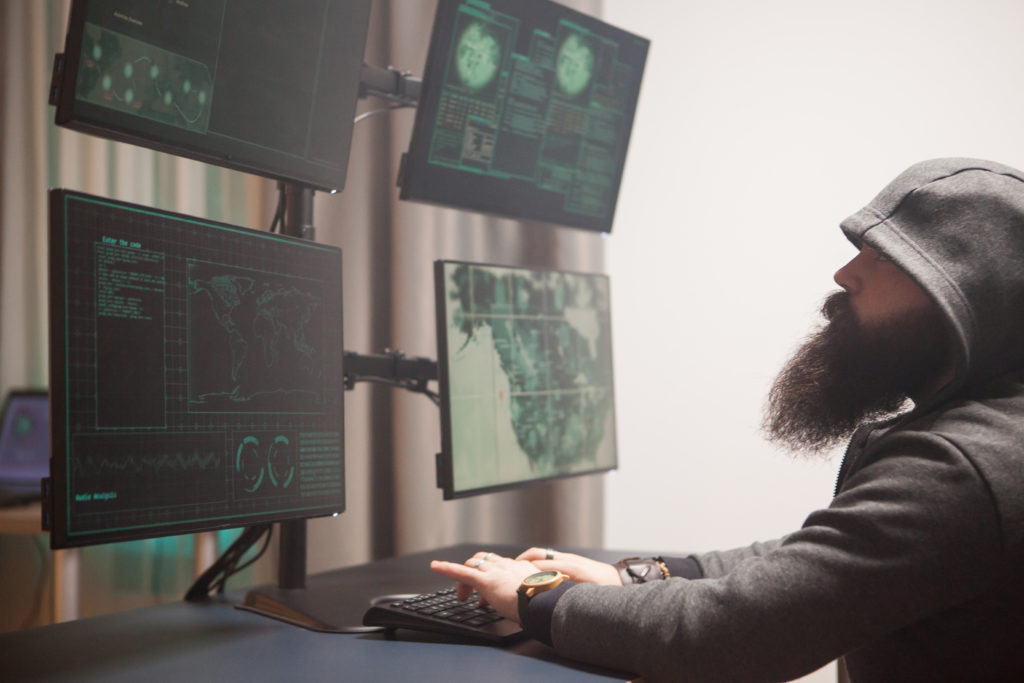 Bearded cyberterrorist wearing a hoodie writing a dangerous virus. Hacker using computer with multiple screens.